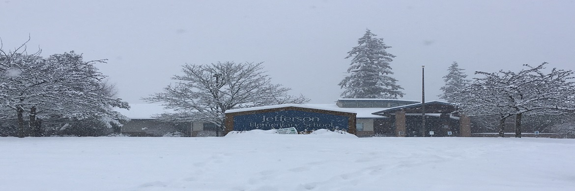 Image of the Jefferson Elementary School sign and school on a snowy day.