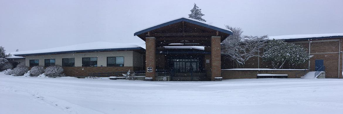 Image of the front of Jefferson School on a snowy day.